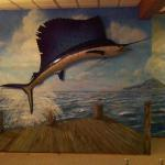 Sailfish Mural by Kristen Muench.  Taxidermied sailfish on the wall jumping over the sea and dock. © Kristen Muench, August 2014 photo by KM.  Private Home Murals.